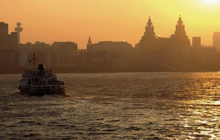 The Mersey Ferry sailing across the river Mersey towards the Liverpool skyline at sunset with the Royal Liver Building in the background.