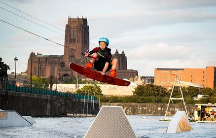 Liverpool Wake Park - Young person wake boarding with Liverpool Cathedral in the background.