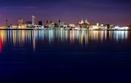 A night time photograph taken from the Birkenhead side of the River in Wirral. The lights from the city are reflected into the water in lots of differ