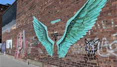Painted wings on a brick wall in the Baltic Triangle. they are the same colour green as the Liver Birds.