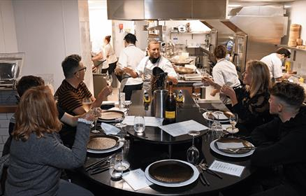 A group of people sitting around a table in the kitchen being served by chef Dave Critchley.