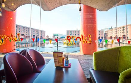 The view through a brightly decorated window, to the Royal Albert Dock on a sunny day.