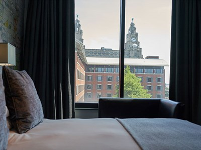 A large double bed with a cream cover and grey pillows with a window to the left with the Liver Building in view