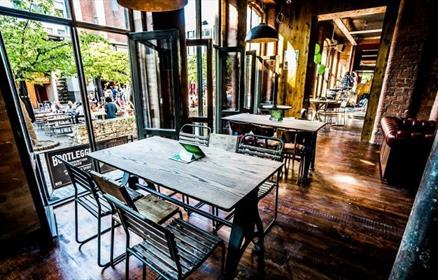 Tables inside McCooleys next to the open windows looking over concert square.