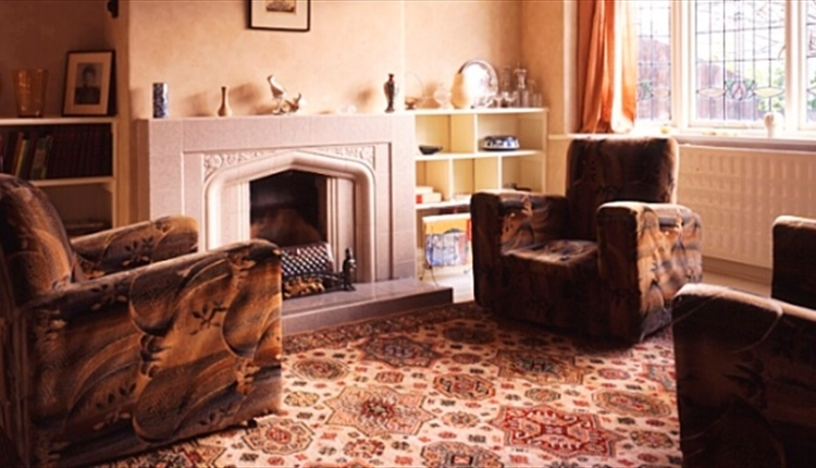 Inside the living room with two brown arm chairs and a brown patterned floor.