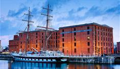 The exterior of the warehouse buildings that the Merseyside Maritime Museum is inside. Outside the museum within the wet dock is a traditional tall sh