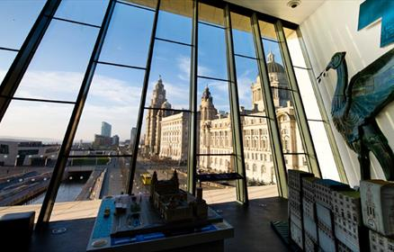 Museum of Liverpool's 'Window with a View' Winner. A huge glass window that looks out across the Pier Head. On the wall next to the window is a life-s