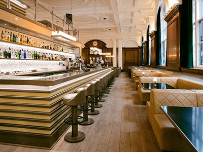 Inside the NYL restaurant and bar. The ceilings are ornate and painted white. The windows to the right are next to plush leather booth seating and mak
