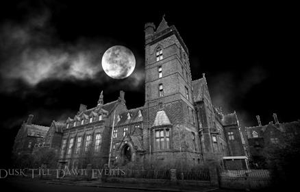 An old hospital building that looks creepy in the dark with a full moon above it