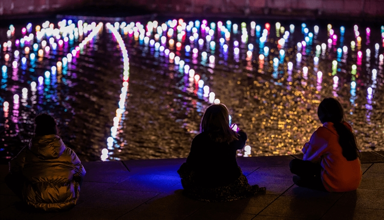 Strings of light float on the water in multi coloured bulbs. Children look on at the lights.