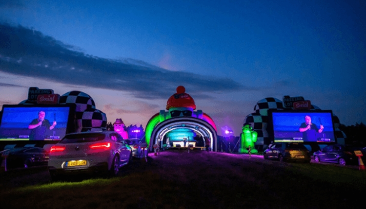 The Parking LOL drive in event at night with neon lights and cars on a field.