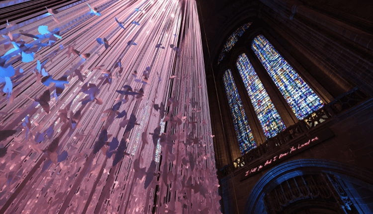 15,000 paper peace doves suspended from the roof inside the Liverpool Cathedral. The artwork has a pink lighting. To the right there is a large colour