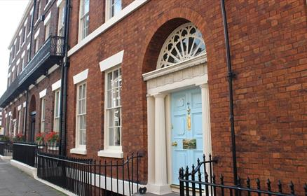 A Georgian Townhouse. The front door is a large pale blue colour with cream pillars. There are original sash windows within the red brick terraced hou