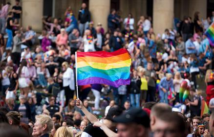 A pride flag is held in the air amongst crowds at St George's Hall