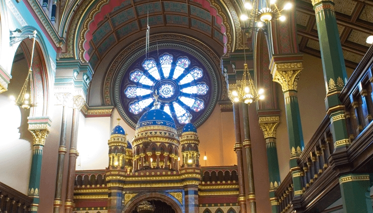 An internal shot of the synagogue showing the ornate architecture. There are details of green, blue and gold.