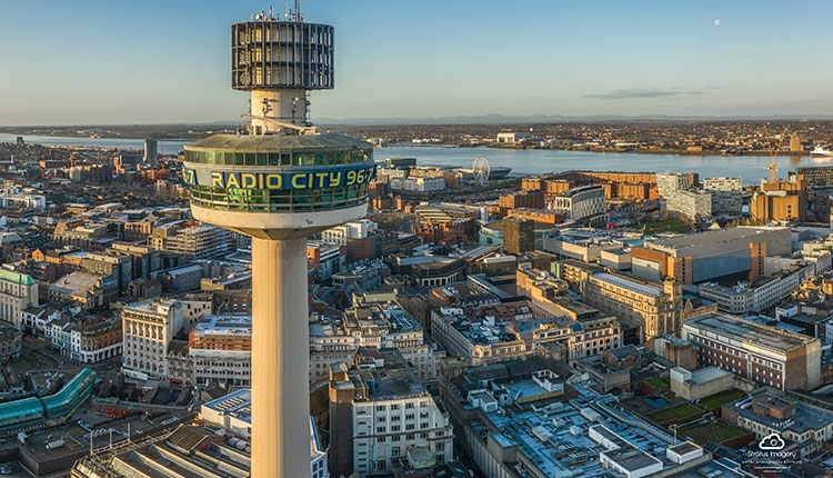 A drone shot of the radio city tower above the city. The shot looks towards the waterfront and the buildings can be seen below.