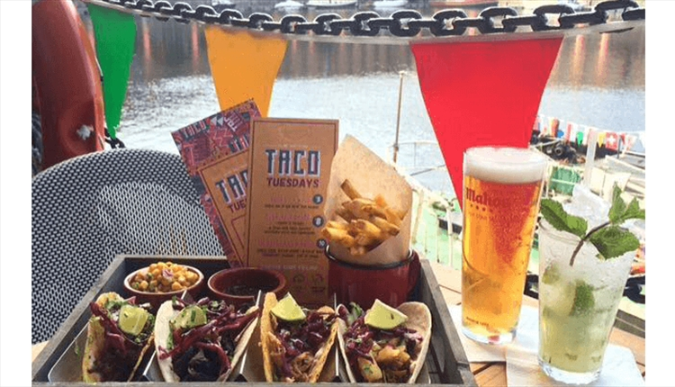 A box is filled with chilli tacos topped with lime and served with a red metal cup filled with fries. A pint of beer and a cuban mojito are on the tab