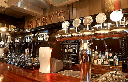 A traditional bar setup with real ale pumps and silver pumps. Behind the bar is wood panelled with 'RIGBY'S' in brass lettering.