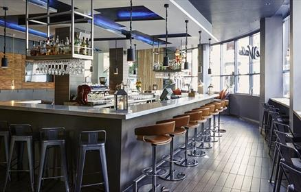 A modern bar with located in the centre of the restaurant. There are metal bar stools lined up against the modern bar which has hanging wine glasses a