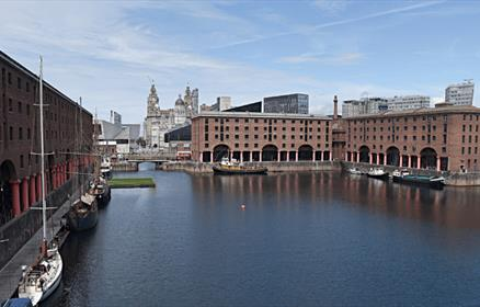 The Royal Albert Dock pavilion water. You can see the warehouse buildings with iconic red pillars. There is a cross section of the Three Graces in the