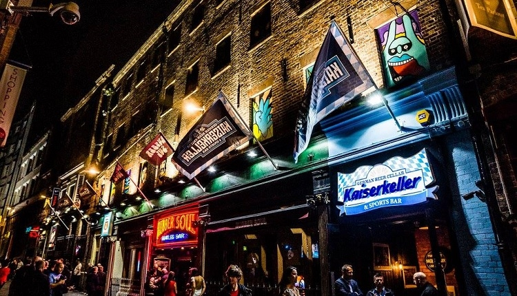 The exterior of the complex. A neon sign reads 'Rubber Soul' in the dark with people seen enjoying drinks on the famous Mathew Street.