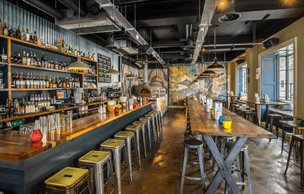 Industrial Style Restaurant showing bar with stools and long tables