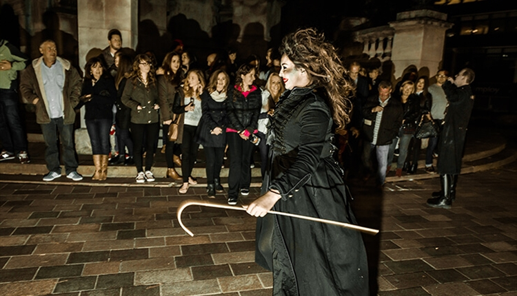 A tour guide dressed up in a spooky costume holding a cane whilst a group of people watch on.