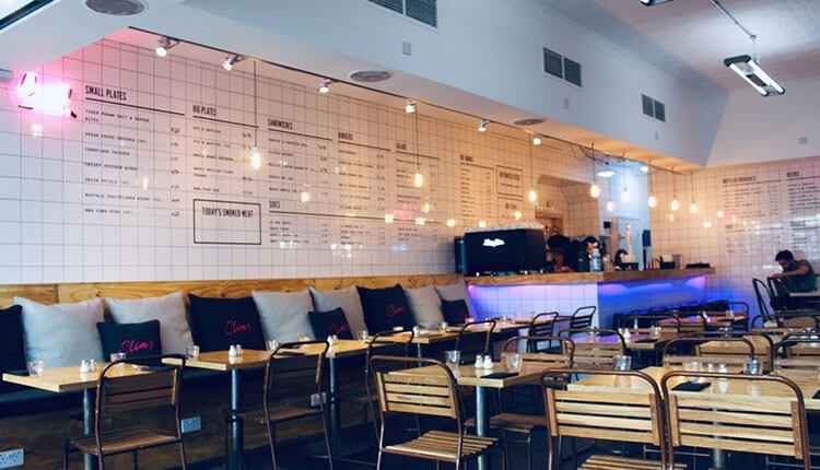 Inside of Slim's with empty tables and menu on the white tiled wall. It has a diner feel with a bright pink neon light that reads 'food -->' There are