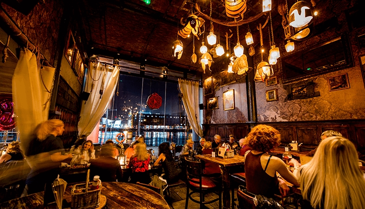 Inside the Smugglers Cove restaurants. It is decorated in a nautical theme, there are people sat at tables and it is dark outside. Looking through the