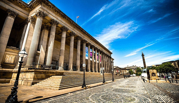 A large neo-classical structure. There are around 12 pillars visible at the top of sand coloured steps. The building is surrounded by cobbles and it i