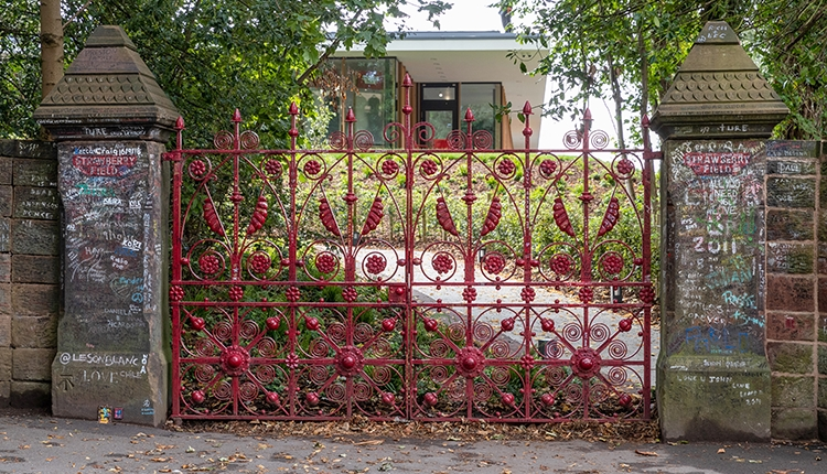 The Red Strawberry Field Gates and gate posts looking through towards the modern centre and lush gardens.