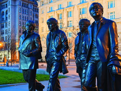 A bronze, larger than life-size statue of The Beatles bathed in a blue hue after sunset. The Three Graces can be seen in the background.