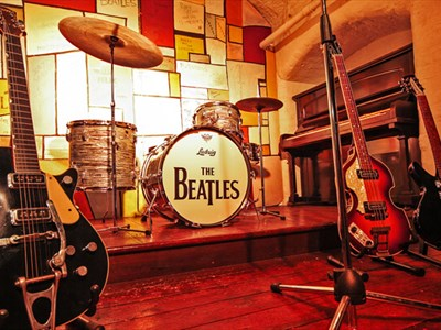 A mock up Cavern Club stage. The middle of the stage features the iconic 'The Beatles' bass drum and 3 guitars.