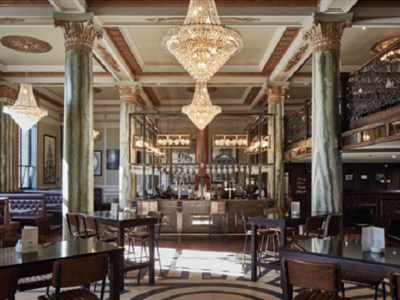 Grand chandeliers hangs from an ornate ceiling there are supported by pillars on a tiled floor.