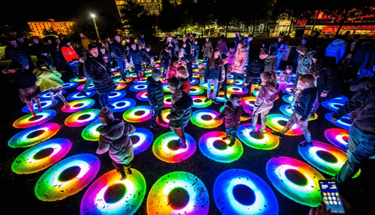 Multicoloured circles of light with children playing.