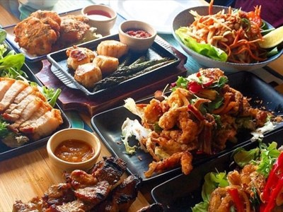 An array of colourful thai food served on small plates and bowls.