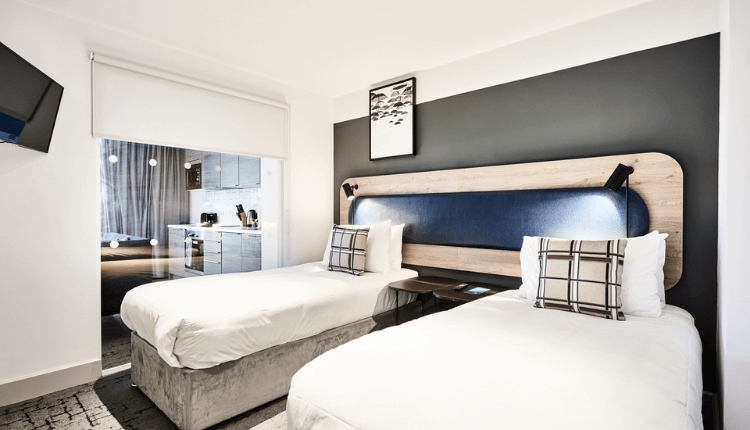 Two twin beds in crisp white linen with nude and brown tartan cushions. The hotel room is modern with a build in kitchen and decorated in neutral tone
