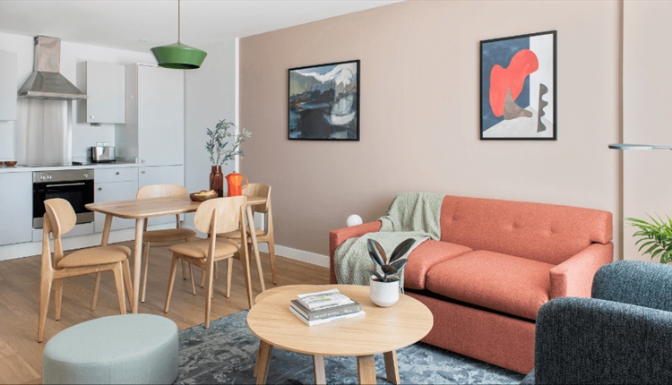 The living area of an apartment with a pink couch, a dining table with four chairs and a kitchen.