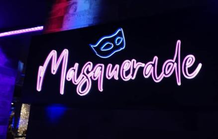 The Masquerade Bar lights up in neon colours on the wall