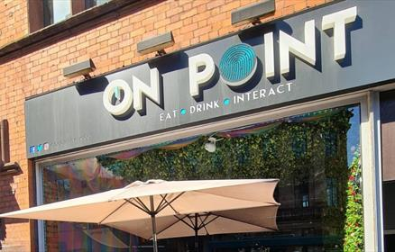 Exterior of On Point Liverpool showing the logo and an umbrella