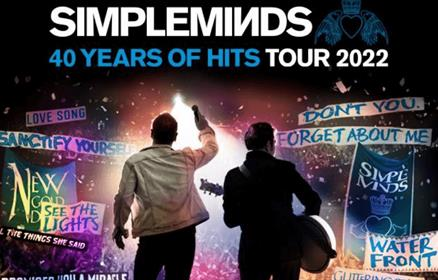 Simple Minds poster showing the back of two people in front of a crowd.