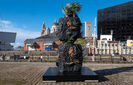 Stacked Heads by Rashid Johnson at Canning Dock - a sculpture with plants on with the backdrop of the three graces.