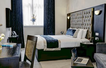 A bedroom in the Richmond with a double bed and dark blue features.