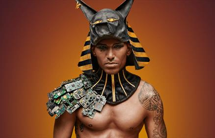A model wearing Egyptian themed head dress and costume.