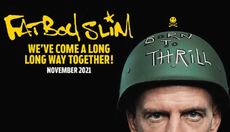 Fatboy Slim wearing a green hat with 'Born to Thrill' written on it on a black background.