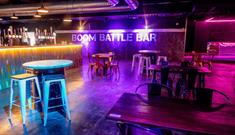 The bar area at Boom Battle Bar with high tables and bright blue and pink lights.