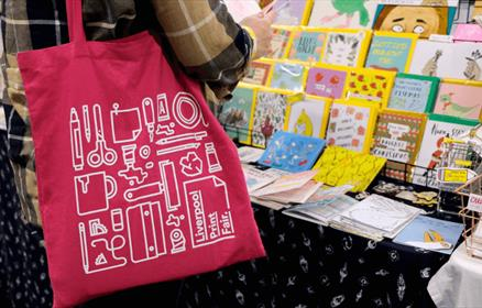 A pink tote bag with a white design on it in front of a stall with cards on.