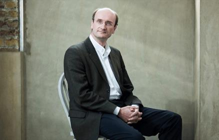 Andrew Manze, conductor, sitting in a chair against a plain wall.