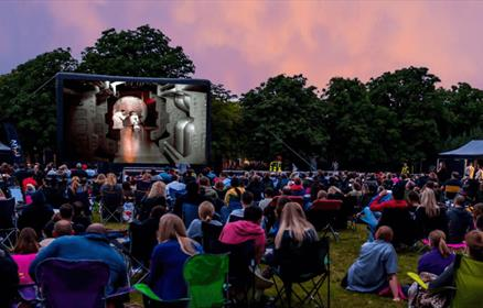 People sitting outside on camping chairs watching a film on a large screen.