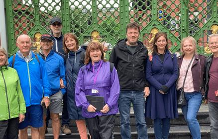 10 people stood in front of a green gate on a tour.